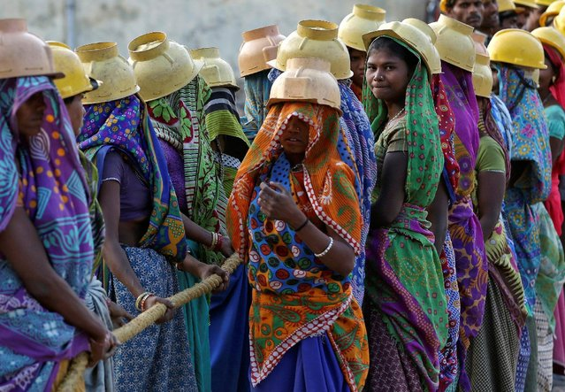 Female labourers wearing helmets take a break from laying underground electricity cables in Ahmedabad, India, March 7, 2016. (Photo by Amit Dave/Reuters)