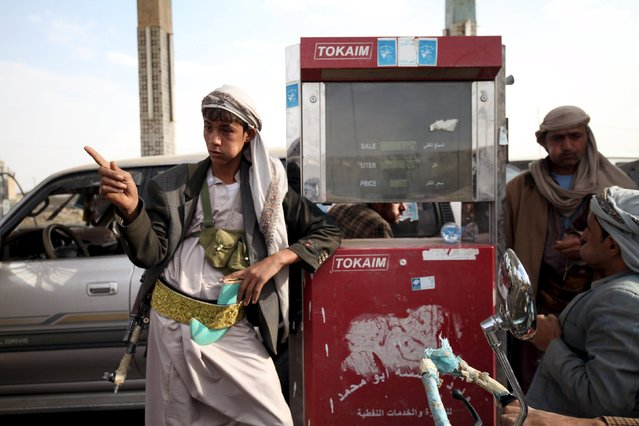 A worker with an AK-47 rifle stops the sale of petrol at a petrol station amid the fuel supply shortage in Yemen's capital Sanaa July 26, 2015. (Photo by Mohamed al-Sayaghi/Reuters)