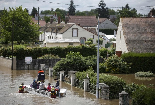 French firefighters on a small boat evacuate residents from a flooded area after heavy rain falls in Chalette-sur-Loing, near Orleans, June 1, 2016. (Photo by Christian Hartmann/Reuters)