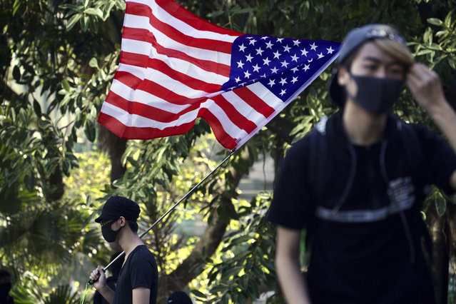 A protester waves an American flag during a rally for students and elderly pro-democracy demonstrators in Hong Kong, Saturday, November 30, 2019. Hundreds of Hong Kong pro-democracy activists rallied Friday outside the British Consulate, urging the city's former colonial ruler to emulate the U.S. and take concrete actions to support their cause, as police ended a blockade of a university campus after 12 days. (Photo by Ng Han Guan/AP Photo)