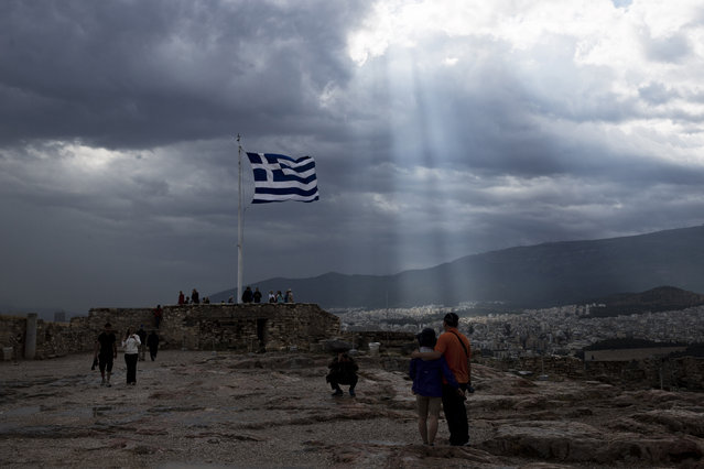 A Greek flag waves as the sunlight filters in through thick clouds on the Acropolis of Athens, in this photo dated Monday, June 22, 2015. The latest incarnation of Greece's economic crisis over the span of a month saw Greece in the end accept harsh austerity measures from creditors to save the country from bankruptcy and possibly ignominiously getting kicked out of the eurozone. (Photo by Petros Giannakouris/AP Photo)