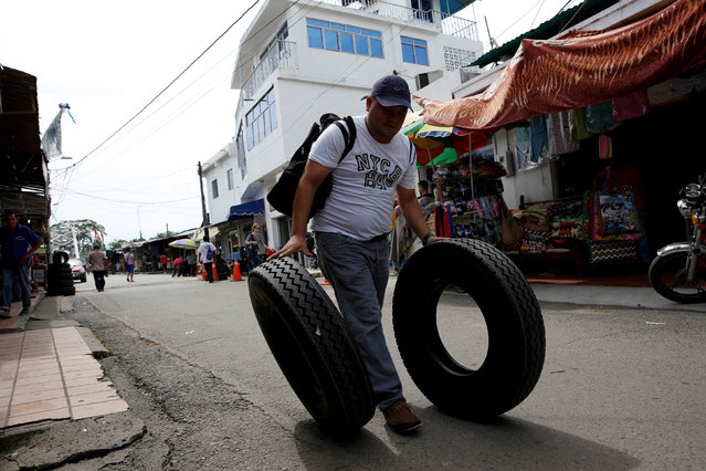 A Venezuelan man pushes tires down the street after buying them in Puerto Santander, Colombia, June 3, 2016. (Photo by Carlos Garcia Rawlins/Reuters)