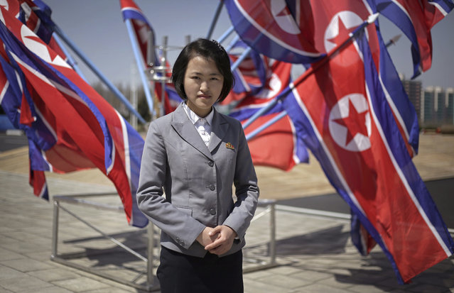 """In this April 13, 2017, photo, Jang Sol Hyang, 19, a Kim Il Sung University student majoring in Mathematics, poses for a portrait at the newly opened Ryomyong Street in Pyongyang, North Korea. Her motto: """"Being a girl doesn't stop me from upholding the leadership of Marshal Kim Jong Un and it drives me to be even better"""". (Photo by Wong Maye-E/AP Photo)"""