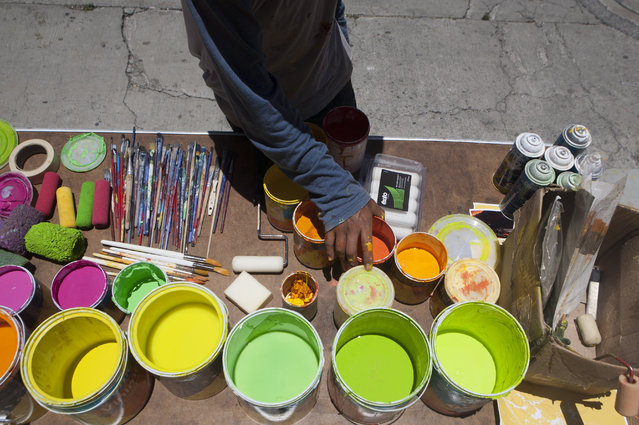 Irving Trejo, of the artist collective German Crew, picks out a can of orange paint while working on a gigantic mural in the Palmitas neighborhood of Pachuca, Mexico, Thursday, July 30, 2015. (Photo by Sofia Jaramillo/AP Photo)
