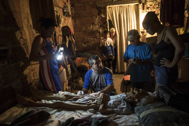 Community activist Carolina Leal uses a cell phone to light up the work area for Roberto Molero as he prepares the body of Teresa Jimenez, 91, after she died of natural causes in her home in Maracaibo, Venezuela, November 17, 2019. Molero embalms bodies with no training other than seeing it done during a decade that he work as a driver at a funeral home, while Leal assumes the role of funeral director in her poor and often violent Maracaibo neighborhood, hoping to rid families of unnecessary misery she's seen too many times. (Photo by Rodrigo Abd/AP Photo)