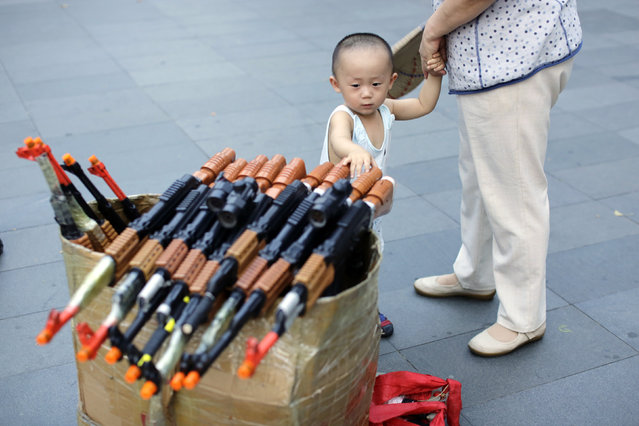 "A boy touches toy guns that are used by local residents to perform revolutionary dances as part of their daily exercise at a square outside a shopping mall in Beijing, June 29, 2014. About 30 local residents formed this ""Nanguan"" art group that enjoys performing and dancing to revolutionary songs as part of their nightly fitness activity. (Photo by Jason Lee/Reuters)"