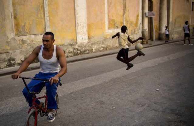 A child rainbow kicks a soccer ball while playing with friends in the streets of Old Havana, Cuba, Tuesday, February 17, 2015. A more relaxed and hopeful atmosphere is evident in Cuba as a result of President Raul Castro's modest reforms and afte the agreement by Cuba and the U.S. to move toward a more normal relationship. (Photo by Ramon Espinosa/AP Photo)