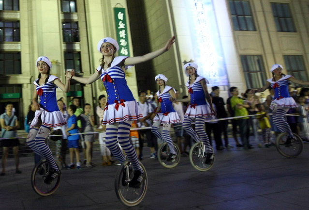 """This picture taken on August 5, 2015 shows performers performing during the opening ceremony of the annual """"Night at the Museum"""" at Beijing Museum of Natural History in Beijing. (Photo by AFP Photo)"""