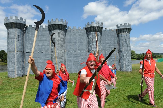 Villagers in revolutionaries' costumes gesture around a wooden and cardboard fortress  and take part in the commemorating of the storming of the Bastille during  Bastille Day, in Lavaré, western France. (Photo by Jean-Francois Monier/AFP Photo)