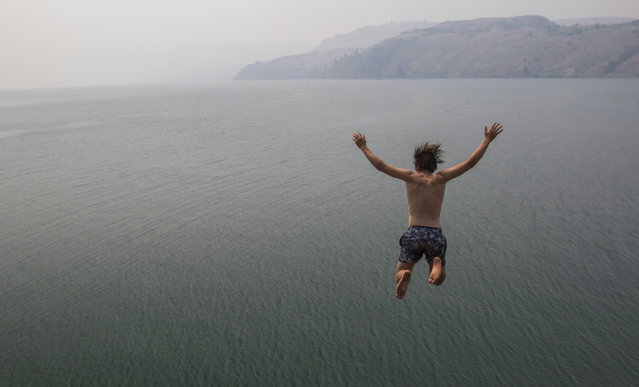 Eli Garlick jumps into Lake Kalamalka in Vernon, British Columbia, Monday, July 17, 2017. The Okanagan area is blanketed with smoke from wildfires burning in the interior of the province. (Photo by Jeff Bassett/The Canadian Press via AP Photo)