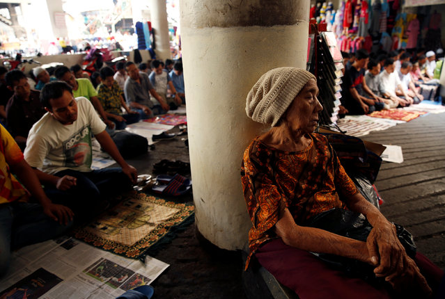 A woman sleeps as Muslims attend Friday prayers during the fasting month of Ramadan at Tanah Abang market in Jakarta, Indonesia, June 24, 2016. (Photo by Reuters/Beawiharta)