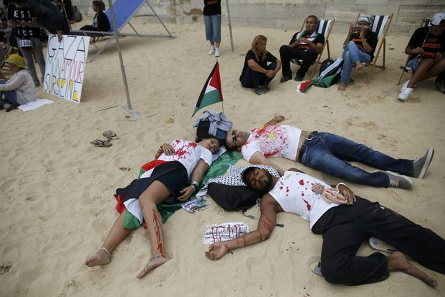 """People covered in mock blood near a Palestinian flag and a placard which reads, """"Gaza – My Love on Seine"""" stage their death on a artificial sand beach at """"Paris Plages"""" to protest the """"Tel Aviv on Seine"""" event, in Paris, France, August 13, 2015. (Photo by Pascal Rossignol/Reuters)"""