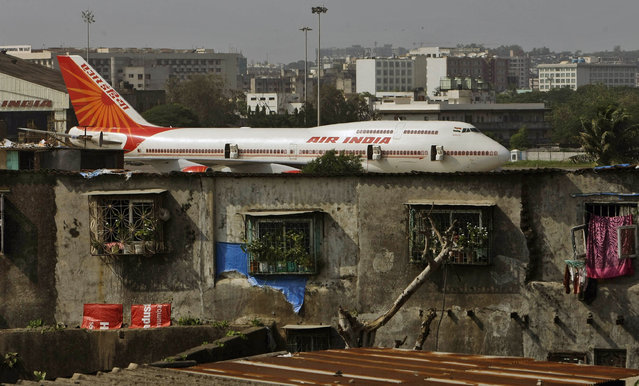 In this May 25, 2010 file photo, an Air India plane is seen in the background of slums adjoining the the international airport in Mumbai, India. Air India says it has set a world record by flying around the world with an all-female crew. Press Trust of India reported that the flight flew over the Pacific Ocean from New Delhi to San Francisco on Monday, and then flew back to New Delhi over the Atlantic on Friday. (Photo by Rajanish Kakade/AP Photo)