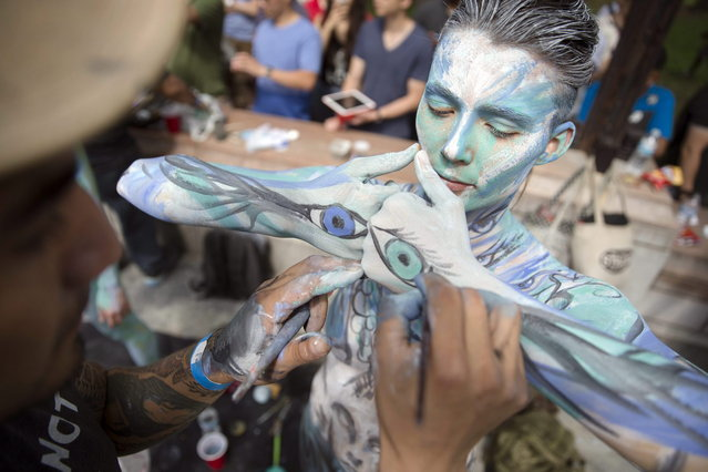 Marion La Coguic, of Portland, Ore., is painted at Columbus Circle as body-painting artists gathered to decorate nude models as part of an event featuring artist Andy Golub, Saturday, July 26, 2014, in New York. Golub says New York was the only city in the country that would allow his inaugural Bodypainting Day. (Photo by John Minchillo/AP Photo)