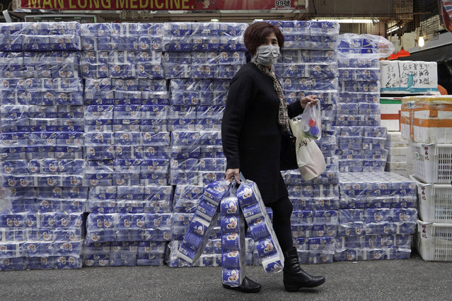 A customer wearing mask carries bath tissue papers she bought at a store in Hong Kong, Saturday, February 8, 2020. Widespread panic-buying of essentials such as toilet rolls and rice has hit in Hong Kong, a knock-on effect of the virus outbreak in mainland China. (Photo by Kin Cheung/AP Photo)