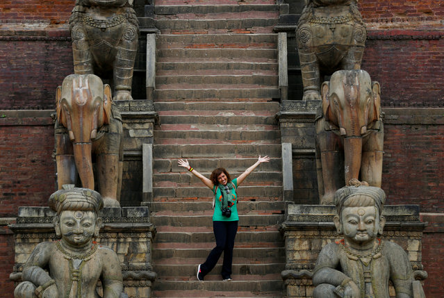 A Tourist poses for picture as she stands in front of the Nyatapola Temple, famous among tourists in Bhaktapur, Nepal August 1, 2017. (Photo by Navesh Chitrakar/Reuters)