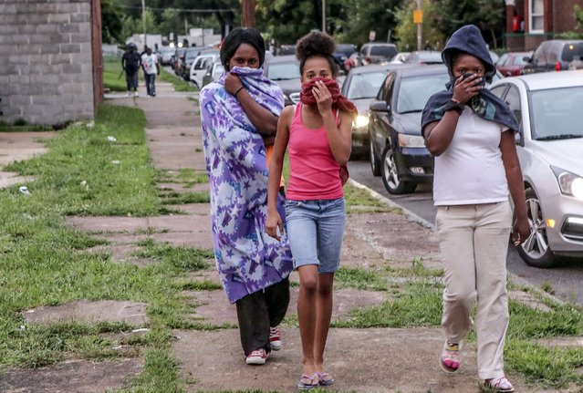 Neighborhood residents cover their faces as the St. Louis Police Department used tear gas to disperse the growing crowd due to a police shooting earlier in the day in St. Louis, Missouri August 19, 2015. (Photo by Lawrence Bryant/Reuters)