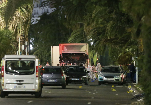 The truck which slammed into revelers late Thursday, July 14, is seen near the site of an attack in the French resort city of Nice, southern France, Friday, July 15, 2016. The truck loaded with weapons and hand grenades drove onto a sidewalk for more than a mile, plowing through Bastille Day revelers who'd gathered to watch fireworks in the French resort city of Nice late Thursday. (Photo by Luca Bruno/AP Photo)