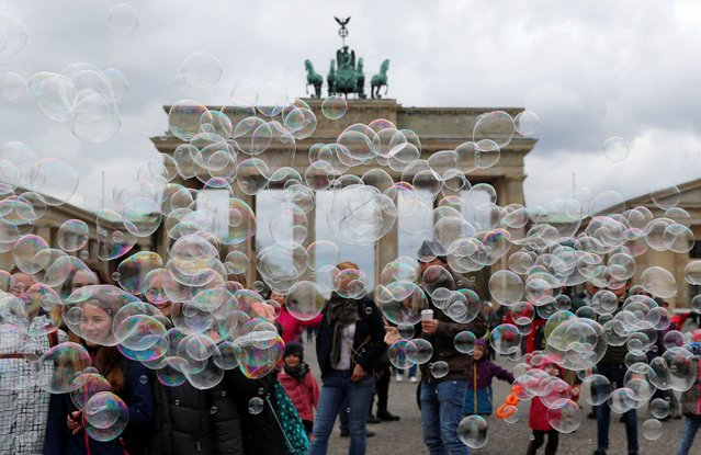 People are seen behind soap bubbles created by a street artist (not pictured) in front of the Brandenburg Gate in Berlin, Germany, April 12, 2019. (Photo by Fabrizio Bensch/Reuters)
