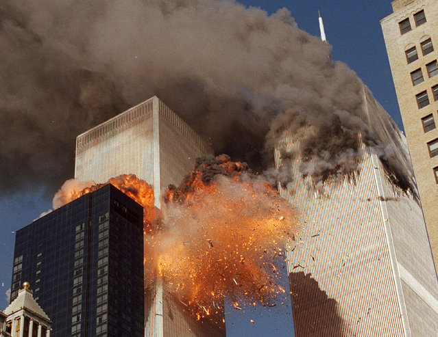 "In this September 11, 2001 file photo, smoke billows from World Trade Center Tower 1 and flames explode from Tower 2 as it is struck by American Airlines Flight 175, in New York. The government is preparing to release a once-classified chapter of a congressional report about the attacks of Sept. 11, that questions whether Saudi nationals who helped the hijackers with things like finding apartments and opening bank accounts knew what they were planning. House Minority Leader Nancy Pelosi said Friday July 15, 2016, that the release of the 28-page chapter is ""imminent"". (Photo by Chao Soi Cheong/AP Photo)"