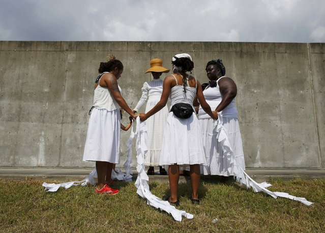 Women pray at the site of the 2005 Industrial Canal levee failure, during a ceremony marking the tenth anniversary of Hurricane Katrina in the Lower 9th Ward in New Orleans, Louisiana August 29, 2015. (Photo by Edmund D. Fountain/Reuters)