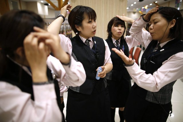 Dynam employees check their if hairstyles are in accordance with regulations, as they receive customer-care training ahead of the grand opening of the company's pachinko parlour in Fukaya, north of Tokyo July 29, 2014. (Photo by Issei Kato/Reuters)