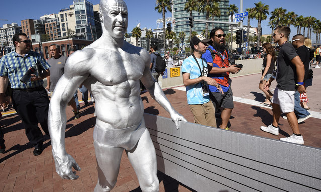 Todd Schimt, dressed as the Silver Surfer, carries his surfboard into the convention center on day one of Comic-Con International held at the San Diego Convention Center Thursday July 21, 2016, in San Diego. (Photo by Denis Poroy/Invision/AP Photo)
