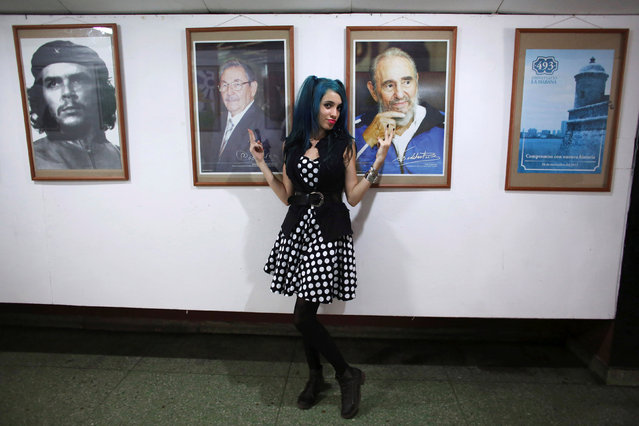"""Bexy Estopina, 21, poses for a photographer (not pictured) in front of pictures of Cuba's former President Fidel Castro (R), Cuba's President Raul Castro (C) and late Cuban revolutionary hero Ernesto """"Che"""" Guevara during the Cuban Otaku festival at a cinema in Havana, Cuba, July 24, 2016. (Photo by Alexandre Meneghini/Reuters)"""