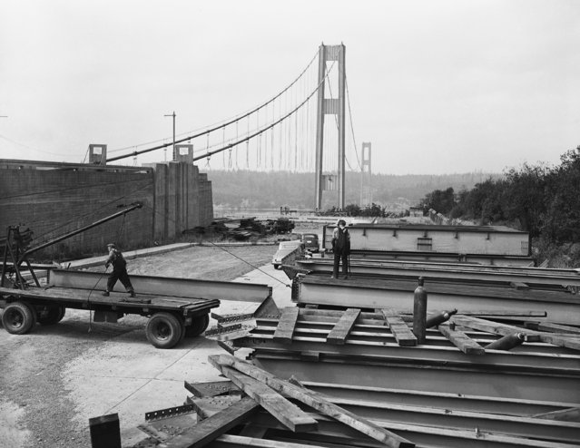 Workmen in foreground are loading steel girders on September 4, 1942 being salvaged from the $6,400,000 Narrows Bridge which collapsed in November 1940 near Tacoma, Washington. The salvage project for WWII defense is expected to yield 3,000 tons of steel wire and 4,500 tons of structural steel from towers (background) which were left standing when the bridge fell. (Photo by Paul Wagner/AP Photo)