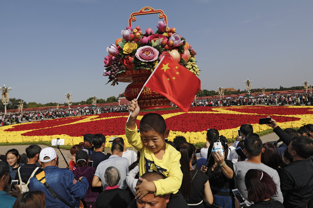 A Chinese boy waves a national flag on his father's shoulder as visitors gather near a giant basket decorated with replicas of flowers and fruits on display at Tiananmen Square on China's National Day in Beijing, Sunday, October 1, 2017. Hundreds of thousands foreign and domestic tourists flock to the square to celebrate the 68th National Day and the Mid-Autumn Festival over the week-long holidays. (Photo by Andy Wong/AP Photo)