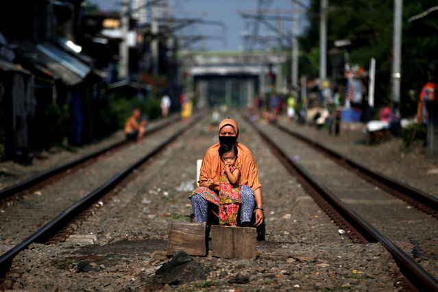 A woman wearing a face mask and a child sit between rail tracks, during the imposition of large-scale social restrictions by the government to prevent the spread of the coronavirus disease (COVID-19) in Jakarta, Indonesia, April 12, 2020. (Photo by Willy Kurniawan/Reuters)