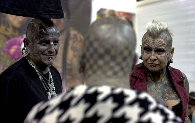 Victor Peralta, from Uruguay, and his wife Gabriela Peralta, from Argentina, talk with Matt Gone, from the U.S., at a tattoo festival in Lima, Peru, Saturday, September 5, 2015. The South American couple hold the official Guinness World Record for married couple with the most body modifications. (Photo by Martin Mejia/AP Photo)