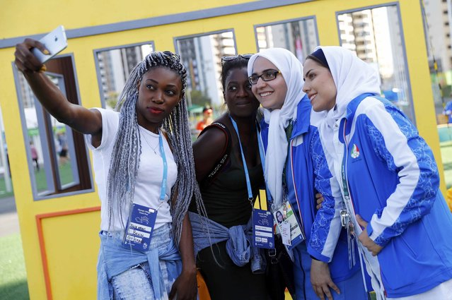 Athletes from Iran (R) have their pictures taken with visitors at the Olympic Village in Rio de Janeiro, Brazil August 1, 2016. (Photo by Kai Pfaffenbach/Reuters)