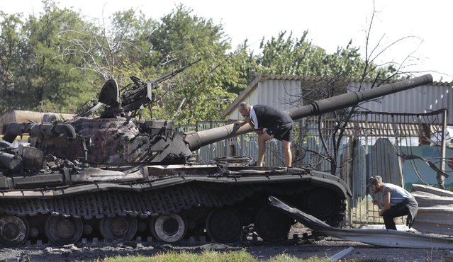 Men inspect a burnt out Ukrainian tank in the village of Kominternovo, on the outskirts of the southern coastal town of Mariupol, September 6, 2014. Russian President Vladimir Putin and Ukraine's President Petro Poroshenko agreed on Saturday in a telephone call that a ceasefire in eastern Ukraine was generally holding but said further steps were needed to make it more durable. (Photo by Vasily Fedosenko/Reuters)