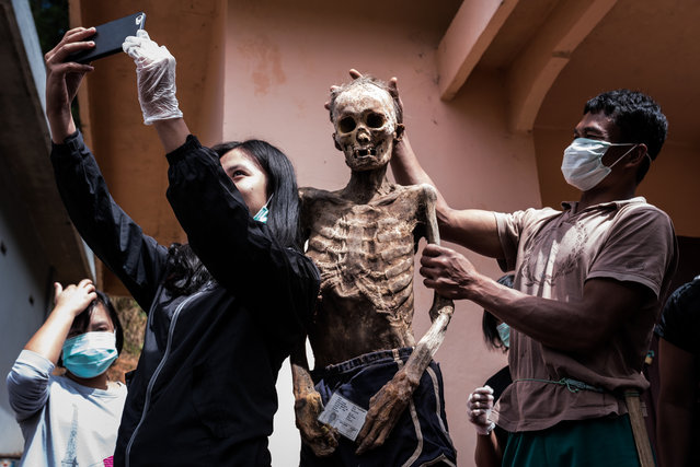 Yuanita takes a selfie with her relative Allo Pongsitammu who passed away roughly 20 years ago. (Photo by Claudio Sieber Photography/The Guardian)