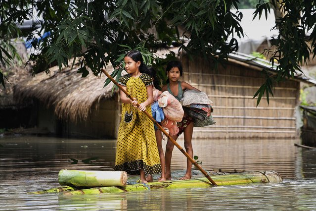 Flood affected children pole a raft in a Burhabrhi village in India, on September 24, 2012. The Assam state government said flood waters there have killed at least seven people and forced nearly a million to leave their homes. (Photo by Anupam Nath/Associated Press)