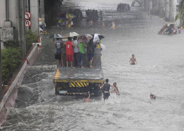 Stranded passengers ride on a truck to cross a flooded street after tropical storm Fung-Wong battered metro Manila September 19, 2014. (Photo by Erik De Castro/Reuters)