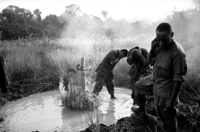 Muddy water in 81mm mortar emplacement filled by monsoon rains splashes over GI's as they fire a round toward a suspected Viet Cong position during an operation about 35 miles southeast of Saigon in Vietnam on July 21, 1966. (Photo by AP Photo)