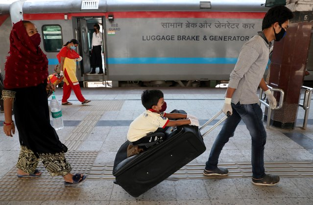 A boy sits on a trolley bag being pulled by his father upon their arrival from New Delhi in a train, after a limited reopening of India's giant rail network, following a nearly seven-week lockdown to slow the spreading of the coronavirus disease (COVID-19), at the Howrah Junction railway station on the outskirts of Kolkata, India, May 14, 2020. (Photo by Rupak De Chowdhuri/Reuters)