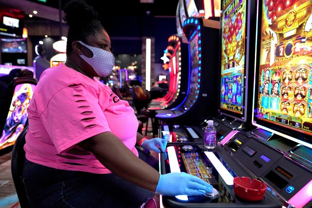 A woman wearing a mask and gloves plays a slot machine at the recently reopened Lucky Star Casino amid the spread of the coronavirus disease (COVID-19), in El Reno, Oklahoma, U.S. May 20, 2020. (Photo by Nick Oxford/Reuters)