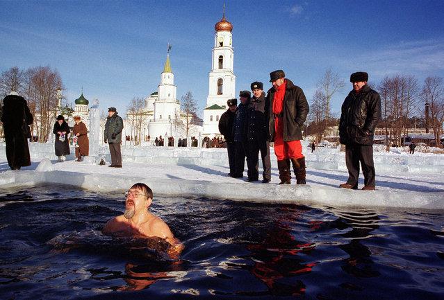 A Russian man bathes in ice-cold water as others pray to mark the Russian Orthodox Epiphany January 19, 2001 near Raifa man''s monastery in Raifa, Tatarstan, Russia as the Russian Orthodox Church marks the Epiphany. Photo by Oleg Nikishin/Newsmakers)