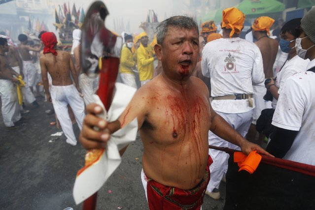 A devotee of the Chinese Bang Neow Shrine who cut himself with an axe, takes part in a procession celebrating the annual vegetarian festival in Phuket September 29, 2014. (Photo by Damir Sagolj/Reuters)