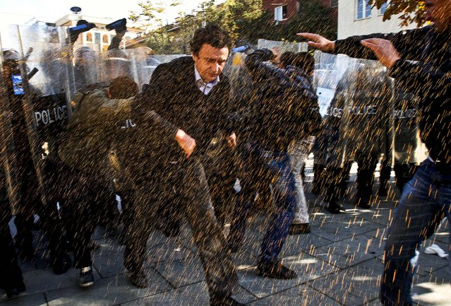 Opposition party leader Albin Kurti, runs through pepper spray used by police to disperse a crowd of anti-Serbia demonstrators protesting a meeting between Prime Minister Hashim Thaci and Serbian leader Ivica Dacic. in  Pristina October 22, 2012. (Photo by Visar Kryeziu/Associated Press)
