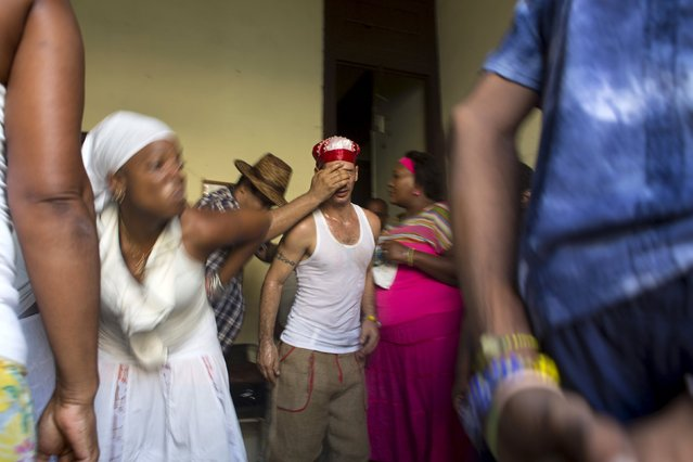 Santeria practitioner Lyan Hernandez, 36, (C) undergoes a brief fit of spirit-induced convulsions during a ceremony to attract spirits of dead ancestors to ask for guidance in downtown Havana, August 18, 2015. (Photo by Alexandre Meneghini/Reuters)