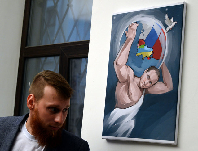 "A visitor visit the ""12 Labors of Putin"" art exhibition on October 6, 2014 marking the 60th birthday of Russia's President Vladimir Putin at the design workshop in Moscow. (Photo by Vasily Maximov/AFP Photo)"