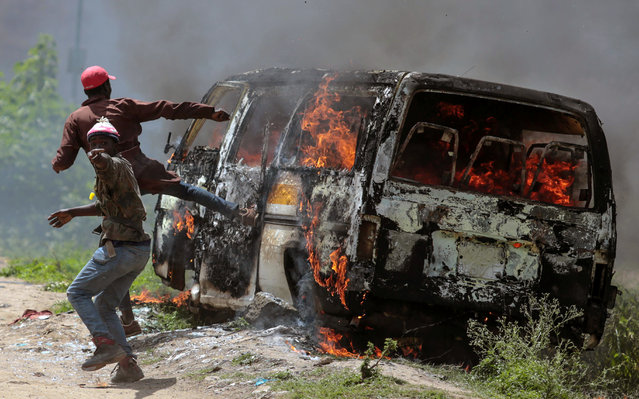 Supporters of Kenyan opposition National Super Alliance (NASA) gesture near a burning vehicle in Embakasi, on the outskirts of Nairobi, Kenya, November 28, 2017. (Photo by Reuters/Stringer)
