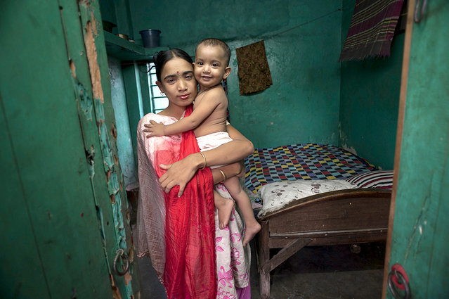 Labone, 27, takes a moment to hold her young daughter Nupur, 1, who was fathered by a client, before she has to return to her evening's work in a brothel in Jessore, Bangladesh. (Photo by Renée C. Byer/Living on a Dollar a Day)