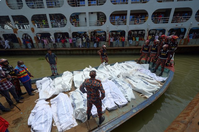 Rescue workers bring bodies of victims after a ferry capsized at the Sadarghat ferry terminal in Dhaka on June 29, 2020. At least 30 people died and a dozen are missing after a ferry capsized and sank on June 29 in the Bangladeshi capital Dhaka following a collision with another vessel, rescue officials said. (Photo by Munir Uz Zaman/AFP Photo)