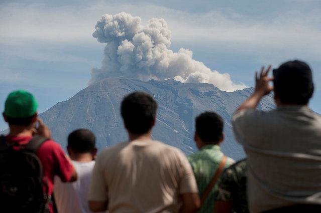 People watch as Mount Agung spews ash and smoke during an eruption from an obeservation post in Rendang, Karangasem, Bali, Indonesia December 9, 2017 in this photo taken by Antara Foto. (Photo by Nyoman Budhiana/Reuters/Antara Foto)