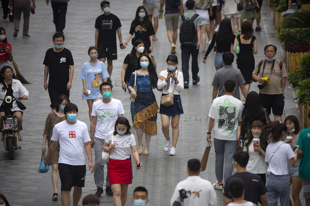 People wearing face masks to protect against the coronavirus walk through an outdoor shopping area in Beijing, Saturday, July 25, 2020. China on Saturday reported several dozen new confirmed coronavirus cases, including a few who caught the virus abroad. (Photo by Mark Schiefelbein/AP Photo)